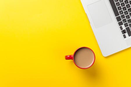 黄色の背景にコーヒーとラップトップ コンピューターのカップ
