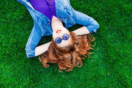 libertad: Mujer pelirroja hermosa que se acuesta en la hierba verde en verano en el parque.