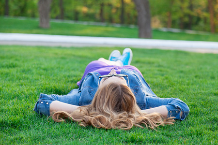 Beautiful blonde women lying down on green grass in summer time in the park.
