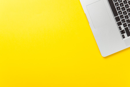 One laptop computer on yellow background, overhead view.