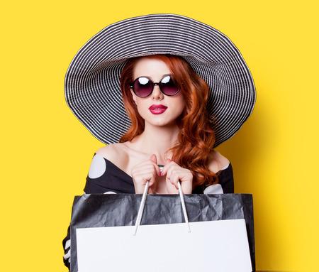 黒のドレスと帽子が黄色の背景上の買い物袋で赤毛の女の子