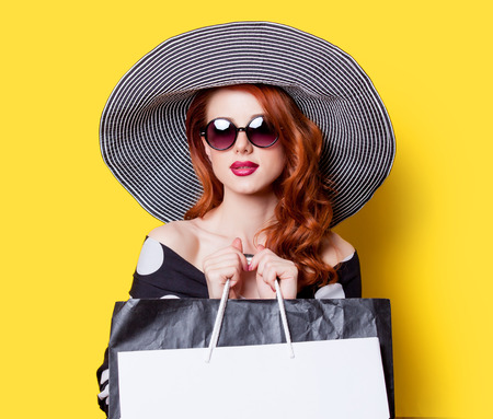 Redhead girl in black dress and hat with shopping bags on yellow background Foto de archivo