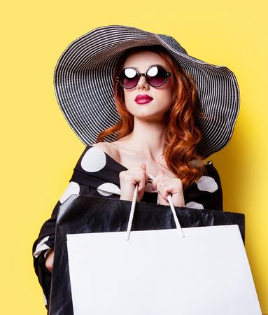 chicas comprando: Chica pelirroja en vestido negro y sombrero con bolsas de la compra sobre fondo amarillo
