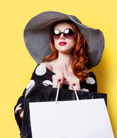 Redhead girl in black dress and hat with shopping bags on yellow background Stok Fotoğraf