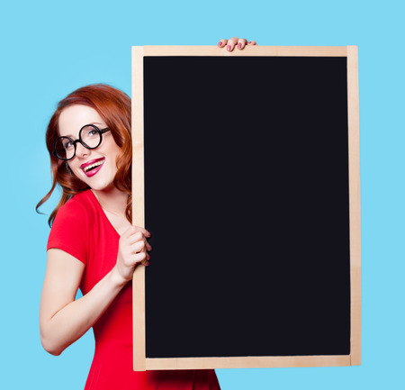 Young smiling redhead student in red dress with blackboard on blue background.