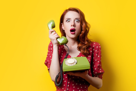 landline: Surprised redhead girl in red polka dot dress with green dial phone on yellow background.