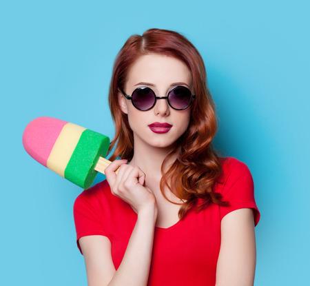 wow: Chica estudiante pelirroja joven en el vestido rojo con el juguete de helado sobre fondo azul.