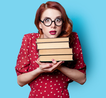 Young redhead teacher in red polka dot dress with books on blue background. Stock Photo