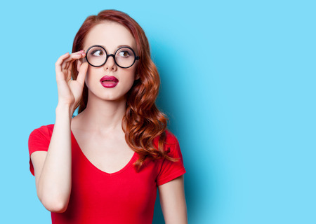 Surprised redhead girl in red dress with glasses on blue background