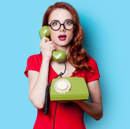 Smiling redhead girl in red dress with green dial phone on blue background.