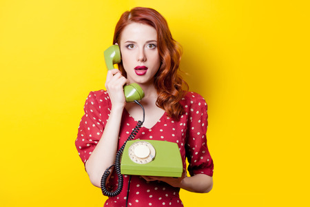 Surprised redhead girl in red polka dot dress with green dial phone on yellow background.
