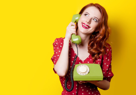 Smiling redhead girl in red polka dot dress with green dial phone on yellow background. Foto de archivo