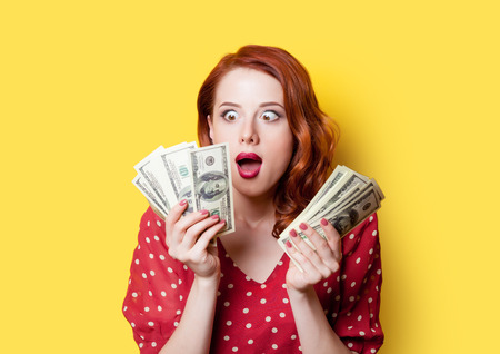 Surprised redhead girl in red polka dot dress with money on yellow background. Standard-Bild