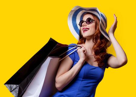 Young redhead girl in blue dress with shopping bags on yellow background.