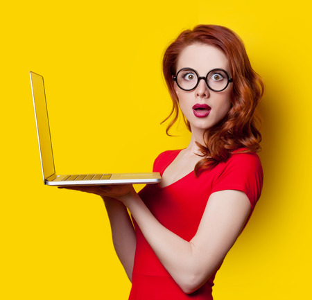 Surprised redhead girl with laptop computer in red dress on yellow background. Stockfoto