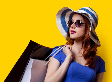 blue dress: Young redhead girl in blue dress with shopping bags on yellow background.