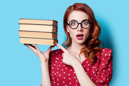 funny people: Young redhead teacher in red polka dot dress with books on blue background. Stock Photo