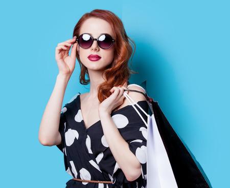 ショッピング バッグの青い背景と黒のドレスで赤毛の女の子 写真素材