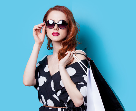 Redhead girl in black dress with shopping bags on blue background Stok Fotoğraf