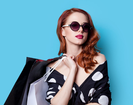 Redhead girl in black dress with shopping bags on blue background Foto de archivo