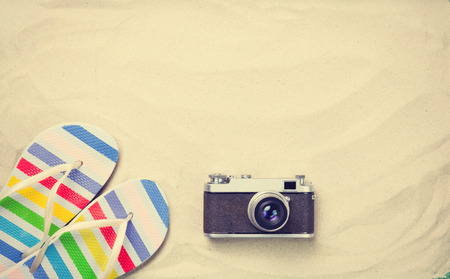 Colorful flip flops and vintage camera on white sand. Photo with high angle view.