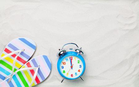 reloj: Chanclas de colores y el clásico reloj de alarma en la arena blanca. Foto con la vista de ángulo alto.