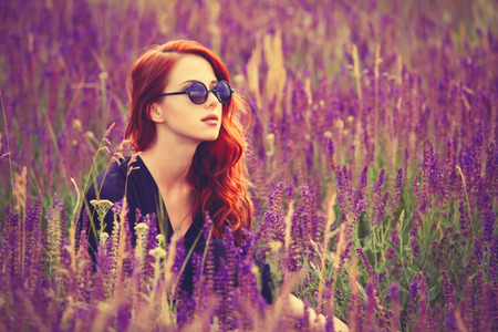 Portrait of a beautiful redhead girl with sunglasses on lavender field.