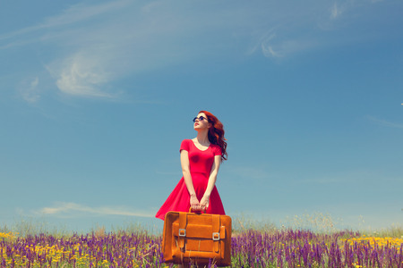free: Portrait of a beautiful redhead girl in red dress with suitcase on the meadow. Stock Photo