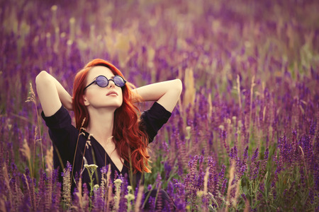 lavender coloured: Portrait of a beautiful redhead girl with sunglasses on lavender field.