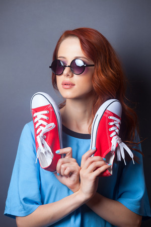 beautiful redhead: Portrait of a beautiful redhead girl in blue dress with red gumshoes on grey background Stock Photo