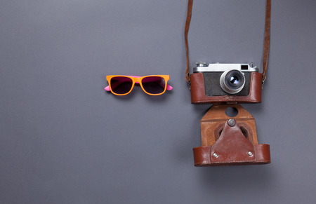 orange glasses and retro camera in leather case lying down on grey background