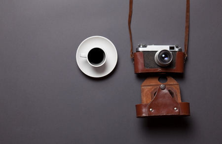 gray backgrund: White cup of coffee and retro camera in leather case on grey background