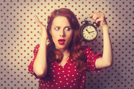 水玉の背景に目覚まし時計で驚いて赤毛の女の子の肖像画。 写真素材