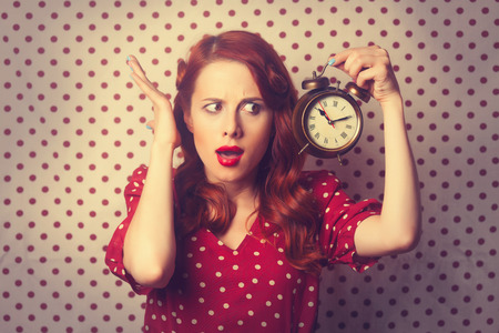 Portrait of a surprised redhead girl with alarm clock on Polka dot background. Standard-Bild