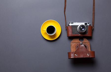 gray backgrund: yellow cup of coffee and retro camera in leather case on grey background Stock Photo