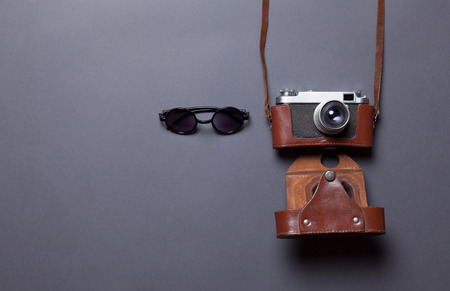 glasses and retro camera in leather case lying down on grey background