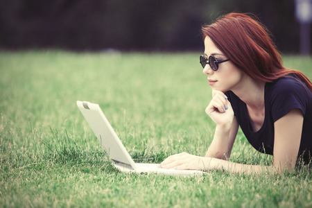 indie: Young girl in indie style clothes with laptop computer on green grass in the park