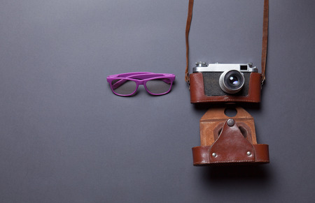 gray backgrund: purple glasses and retro camera in leather case lying down on grey background