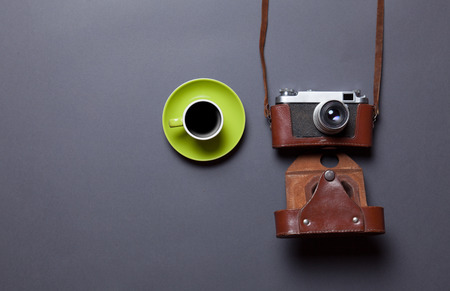 green cup of coffee and retro camera in leather case on grey background