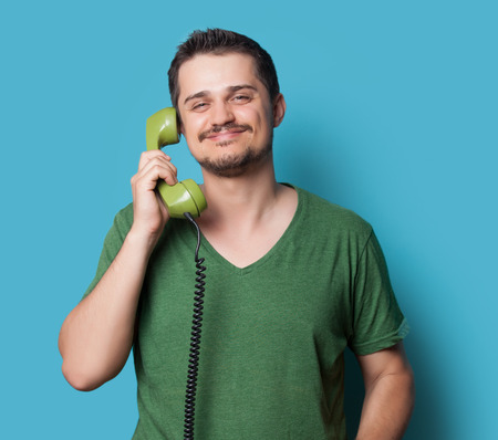 green clothes: young guy in t-shirt with green retro dial phone on blue background. Stock Photo