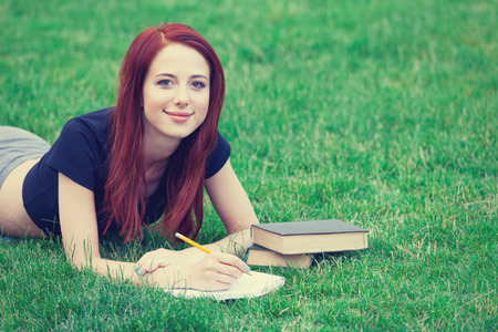 indie: Young girl in indie style clothes with books on green grass in the park