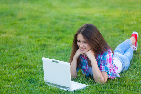 grass beautiful: Young teen girl with white laptop computer lying down on green grass in the park