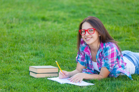 grass beautiful: Young teen girl with white books and notebook lying down on green grass in the park Stock Photo