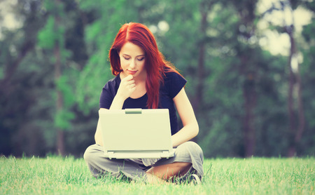 indie: Young girl in indie style clothes with notebook on green grass in the park