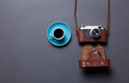 blue cup of coffee and retro camera in leather case on grey background