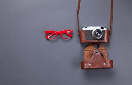 gray backgrund: red glasses and retro camera in leather case lying down on grey background Stock Photo