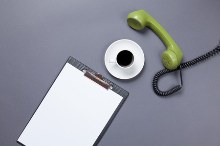 phone handset: Business board and cup of coffee with green dial phone handset on grey background