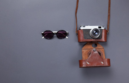 gray backgrund: glasses and retro camera in leather case lying down on grey background