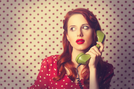vogue style: Portrait of a redhead girl with green dial phone on Polka dot background.