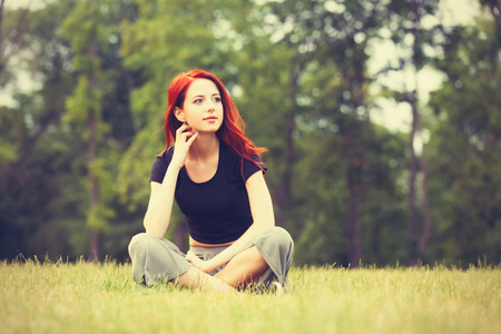 indie: Young girl in indie style clothes on green grass in the park Stock Photo